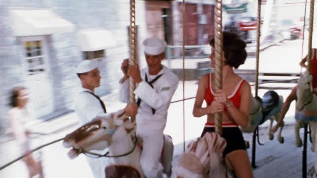 vidéos et rushes de 1965 wide shot two sailors and  a young woman flirting on merry-go-round - marinière
