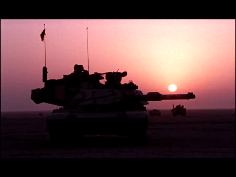 Wide shot two soldiers in M1 Abrams tank in desert at sunset/ Kuwait