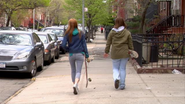 Wide shot Two teenage girls carrying skateboards and walking on city sidewalk / Brooklyn, New York, USA