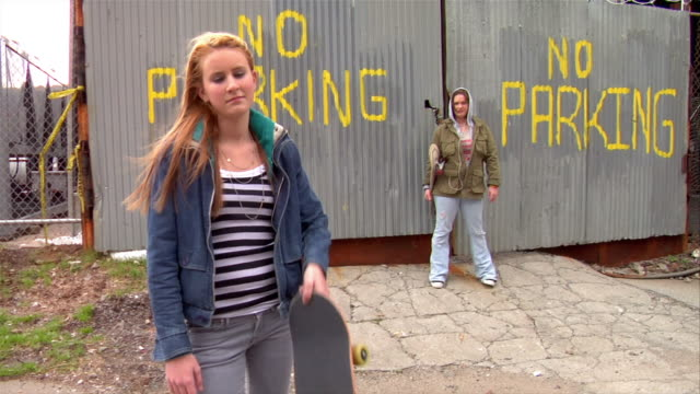 wide shot two teenage girls holding skateboards and standing near no parking sign spray painted on fence / brooklyn, new york, usa - no parking sign stock videos & royalty-free footage