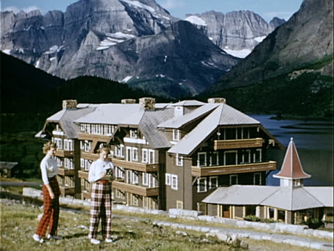 1951 wide shot two teenage sisters standing on hill near chalet and lake at base of rocky mountains in british columbia glacier national park / montana , usa  - コテージ点の映像素材/bロール