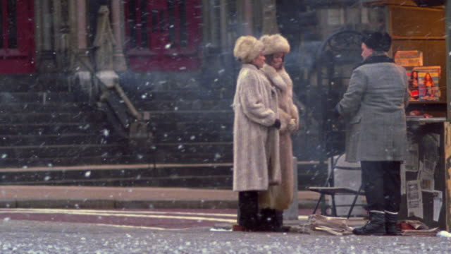wide shot pan two woman wearing fur coats + hats buying magazine from newsstand with snow falling - 毛皮のコート点の映像素材/bロール