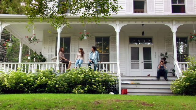 wide shot two women and man sitting on porch and waving/ roxbury, new york - front stoop stock videos and b-roll footage