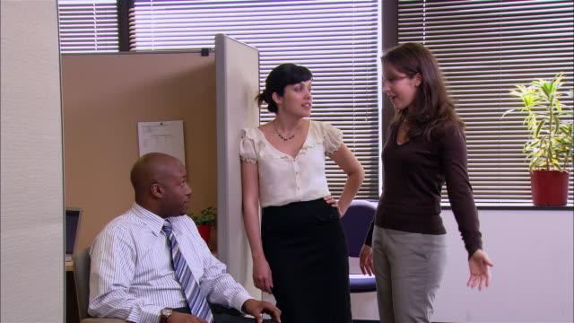 vídeos de stock, filmes e b-roll de wide shot two women and man talking outside cubicle / portrait of co-workers smiling at camera - menos de 10 segundos