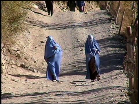 2002 wide shot two women in blue burkas walking on a dirt road toward cam / afghanistan - 若い女性だけ点の映像素材/bロール