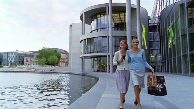 wide shot two women laughing and shopping / pan over water / government district, berlin - arm in arm stock videos & royalty-free footage