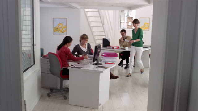 stockvideo's en b-roll-footage met wide shot two women meeting at desk in office/ man joining meeting/ one woman making phone call while another approaches with document as man leaves/ paris - tijdslimiet