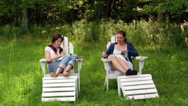 wide shot two women sitting in adirondack chairs flipping through magazines and talking - アディロンダックチェア点の映像素材/bロール