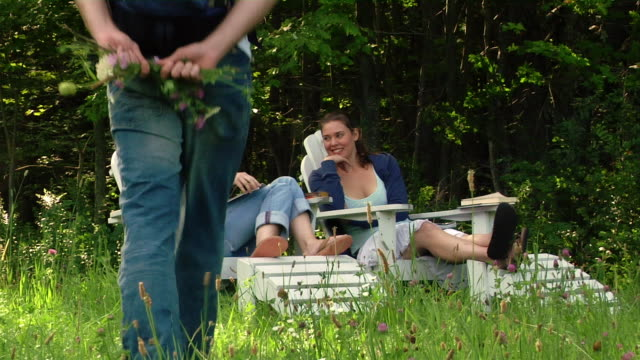 wide shot two women sitting in adirondack chairs on edge of woods / man walking up and presenting them with wildflowers - maschio con gruppo di femmine video stock e b–roll