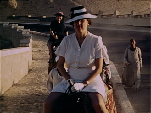 stockvideo's en b-roll-footage met 1939 wide shot two women tourists riding camels led by men along road / cairo, egypt  - 1939