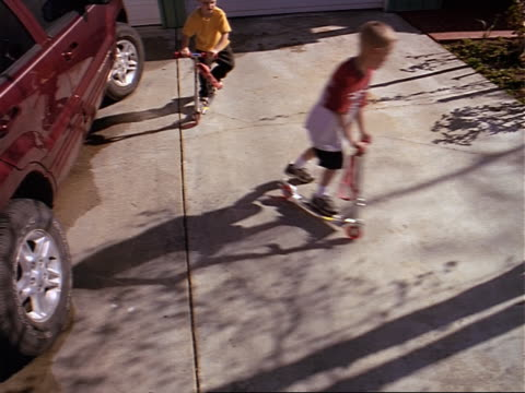 wide shot two young boys play on their driveway by riding their scooters in a circle - driveway stock videos & royalty-free footage