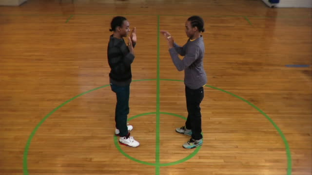 vídeos de stock, filmes e b-roll de wide shot two young men giving each other street handshake and dancing on basketball court / new york city, new york, usa - simetria