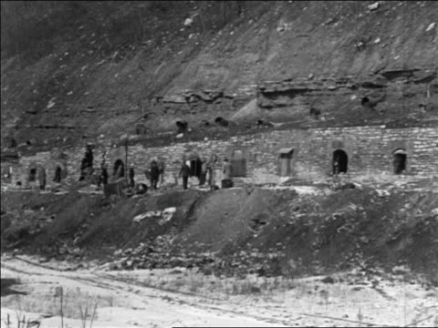 vidéos et rushes de b/w 1935 wide shot unemployed miners walking in front of abandoned coke ovens / pennsylvania / newsreel - pennsylvanie
