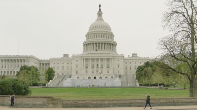 stockvideo's en b-roll-footage met wide shot us capitol with mask wearing people walking - united states congress