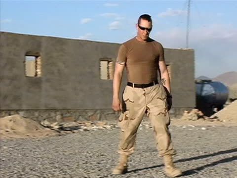 Wide shot US soldier running to catch football/ Afghanistan