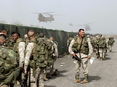 stockvideo's en b-roll-footage met wide shot us soliders congregating by fence as helicopters land in background - operation enduring freedom