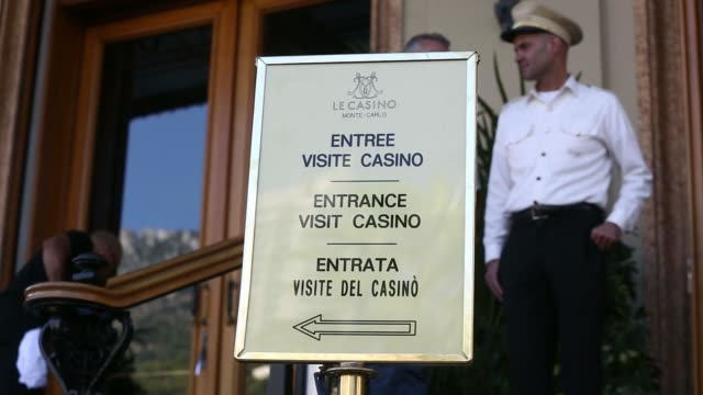 Wide shot vehicles drive past the Casino de Monte Carlo in Monaco France on Friday Sept 26 A sign sits above the casino entrance An entrance sign on...
