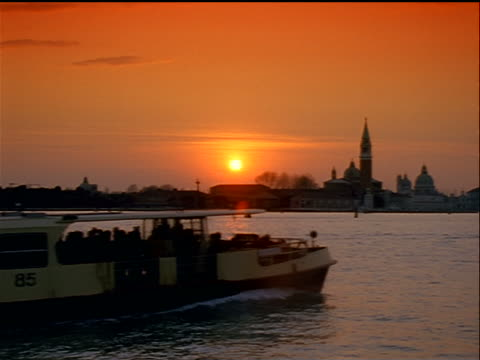 wide shot venice skyline at sunset with water in foreground / tour boat/water taxi passing in foreground / italy - water taxi stock videos & royalty-free footage