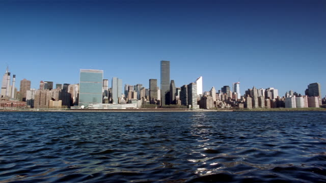wide shot view across east river of manhattan skyline with united nations at left / new york city - citigroup center manhattan stock videos & royalty-free footage