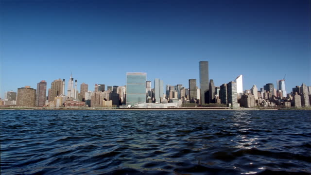 wide shot view across east river of manhattan skyline with united nations in center / new york city - citigroup center manhattan stock videos & royalty-free footage