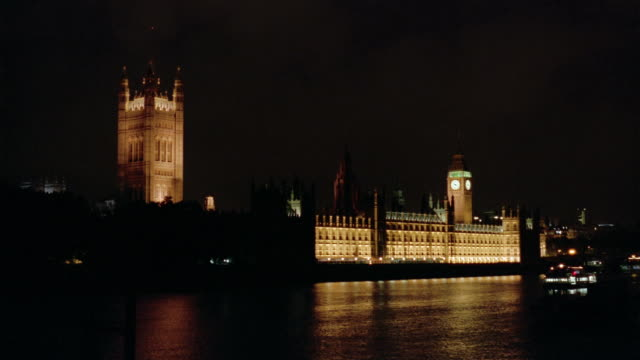 wide shot view across thames of westminster palace lit up at night / barges sailing on river / london - victoria tower stock videos & royalty-free footage