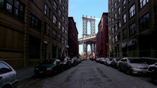 wide shot view down street in dumbo neighborhood of manhattan bridge / brooklyn, new york city - urban road stock videos & royalty-free footage