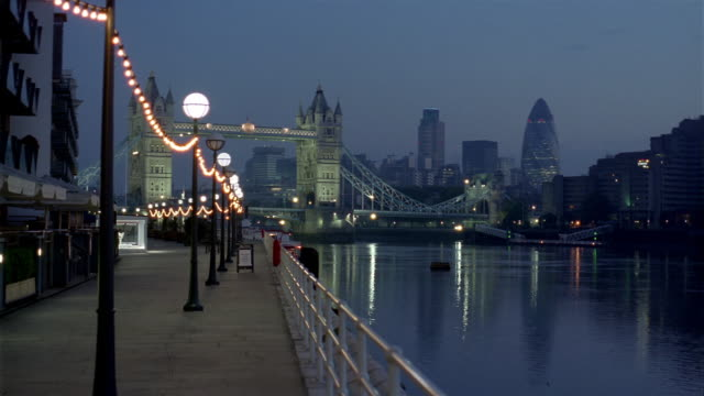 wide shot view from promenade along river thames of tower bridge and skyline at twilight / london - promenade stock videos & royalty-free footage