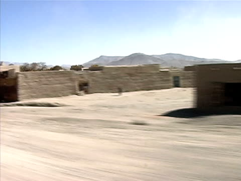 Wide shot view of buildings and landscape from vehicle/ Afghanistan