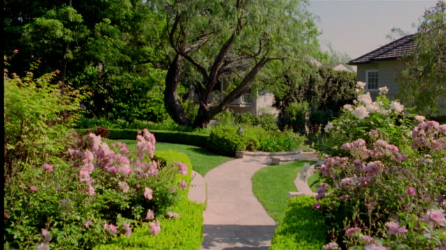 wide shot view of garden and path leading to house - garden path stock videos and b-roll footage