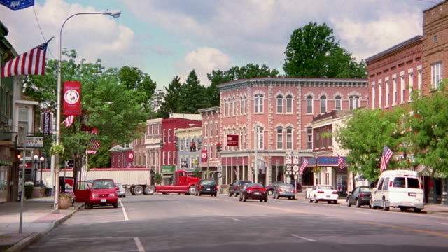 wide shot view of light traffic on main street in small town - city street stock videos & royalty-free footage