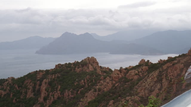 wide shot view of mountains and water/ pan close up couple looking out over windshield of parked convertible/ corsica - 年の差カップル点の映像素材/bロール