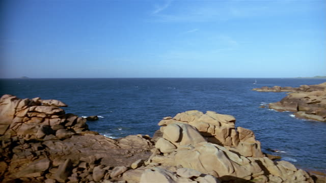 vidéos et rushes de wide shot view of rocks and  water / pan to tourists at the base of lighthouse / ploumanach - bretagne