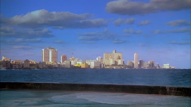 wide shot view of santo domingo skyline with sea spray splashing onto pier in foreground / dominican republic - サントドミンゴ点の映像素材/bロール