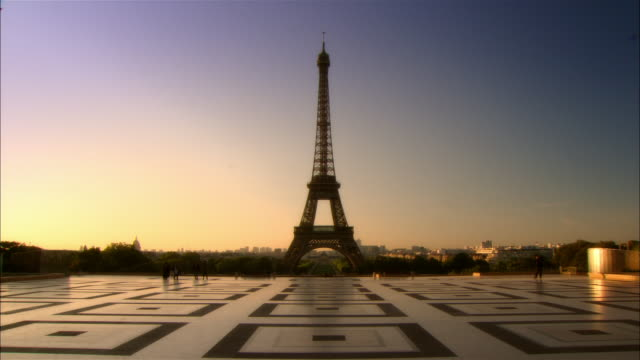 vidéos et rushes de wide shot view of the eiffel tower across the esplanade des droits de l'homme from the palais de chaillot - aube