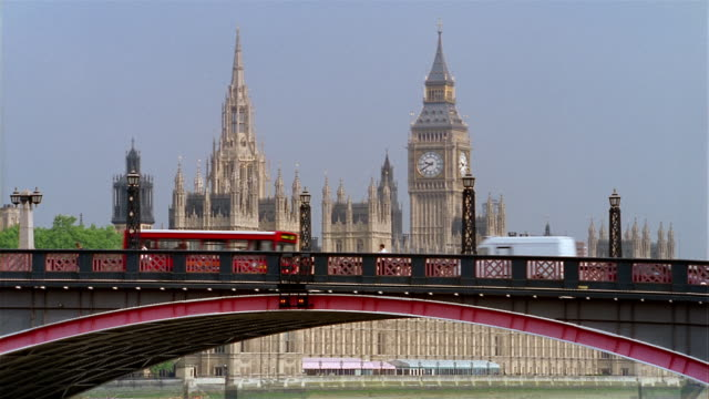 Wide shot view of traffic crossing Lambeth Bridge, Big Ben and spires of Westminster Palace / London