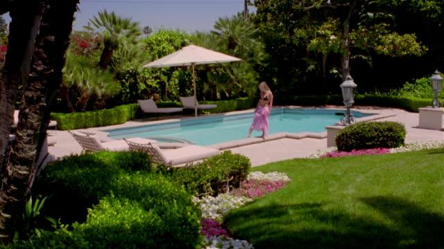vídeos y material grabado en eventos de stock de wide shot view of woman walking poolside / dipping her foot into swimming pool in backyard area / lying down on lounge chair - acostado