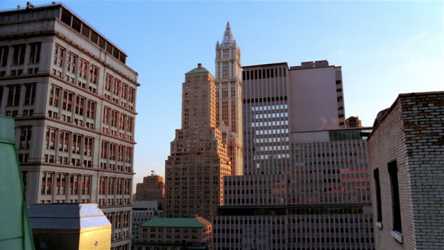 wide shot view of woolworth building and surrounding buildings in lower manhattan at dawn / new york city - woolworth building stock videos & royalty-free footage