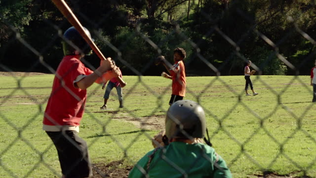 vídeos y material grabado en eventos de stock de wide shot view through fence of boy pitching baseball / boy swinging and missing ball - batear