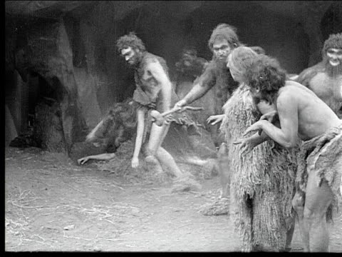 1914 B/W Wide shot Violent cavemen carrying young cavewomen and beating old cavewoman