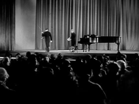 Wide shot Violinist Jascha Heifetz and pianist standing in front of audience and walking off stage after performance/ USA