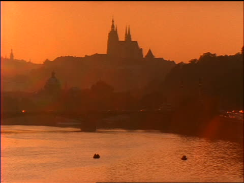 wide shot vltava river with silhouette of castle in background at sunset / prague, czech republic / red filter - フラッチャニ城点の映像素材/bロール