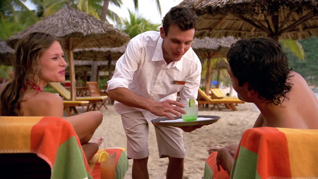 Wide shot waiter serving drinks to couple sitting in lounge chairs on beach / man and woman toasting