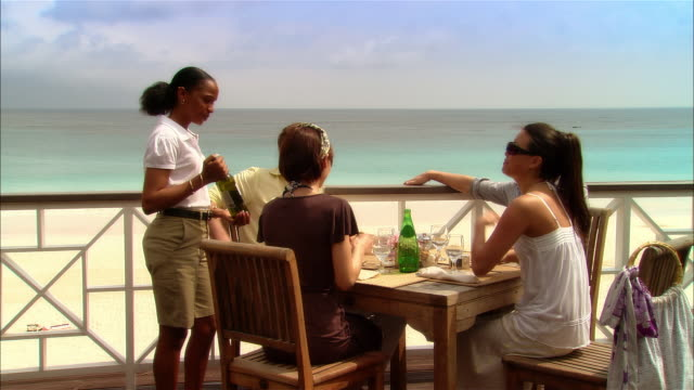 Wide shot Waitress showing wine bottle to young couples at seaside restaurant during vacation/ Harbor Island, Bahamas