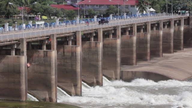 wide shot water from the chao praya river passes through radial sluice gates at the chao praya dam in subpaya district chainat province thailand wide... - チャオプラヤ川点の映像素材/bロール