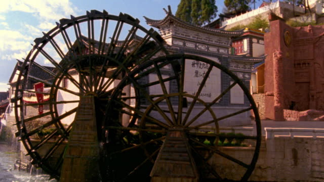 wide shot water wheels spinning with traditional building in background / lijiang, yunnan province, china - mill stock videos & royalty-free footage