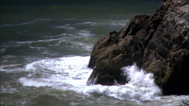 vídeos de stock e filmes b-roll de wide shot waves crashing on rocky coast/ malibu, california - pacífico norte