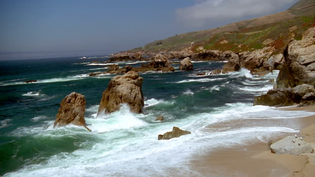 Wide shot waves lapping against rocks in water off coastline / Carmel, California