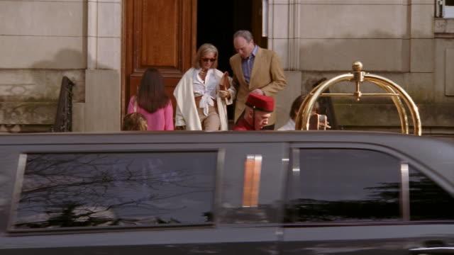 vídeos y material grabado en eventos de stock de wide shot wealthy man and woman leaving hotel + getting into limousine / bellman pushing luggage - hospitalidad
