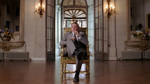 Wide shot wealthy man sitting in gilded chair in foyer of mansion / shifting in chair / looking at CAM