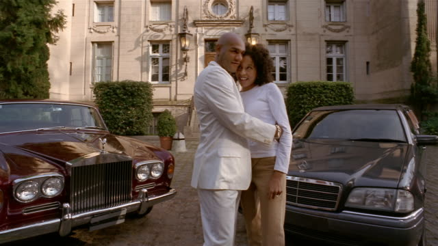 wide shot wealthy young man and woman dancing in front of luxury cars + mansion / looking at cam - rolls royce stock videos and b-roll footage